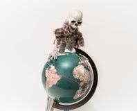 Ansicht des menschlichen lustigen Skeletts im abgenutzten Stoff, der unten auf Weltkugel schaut Stockfotografie