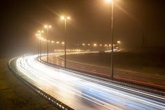 Ansicht des Nachtweges mit Spurnscheinwerferautos Lizenzfreies Stockfoto