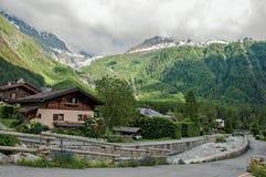 Ansicht des Nebenflusses, der Häuser und der alpinen Landschaft am französischen Dorf von Argentière Stockfotografie