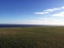Ansicht des Ozeans auf einem grasartigen Feld Lizenzfreies Stockfoto