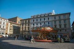 Ansicht des Quadrats mit Gebäuden, Leuten und Karussell bei dem Sonnenuntergang in Florenz Lizenzfreies Stockbild