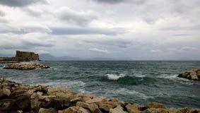 Ansicht des rastlosen Golfs von Neapel mit einer groß-aussehenden Welle und einem Schloss Castel Dell-` ovo Stockfoto