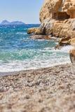 Ansicht des sandigen Strandes, des sealine, der Wellen, der Klippe und des blauen Himmels am sonnigen Tag des Sommers Lizenzfreie Stockfotografie