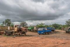 Ansicht des Schrottes mit einigen Packwagen baute und andere Fahrzeuge, Regenwald und bewölkter Himmel als Hintergrund ab stockfotografie