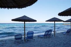 Ansicht des Seestrandes mit Regenschirmen und sunbeds am Abend Lizenzfreie Stockfotografie