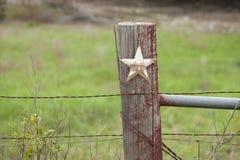 Ansicht des selektiven Fokus des grungy Sternes auf altem Zaunbeitrag in Texas Lizenzfreies Stockfoto