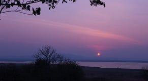 Ansicht des Sonnenuntergangs am See und am Berg, Thailand Lizenzfreies Stockfoto