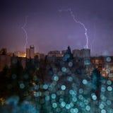 Ansicht des Stadtsturms durch nasses Fenster mit unscharfem Regen fällt Stockfotografie