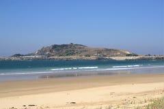 Ansicht des Steinbruchhügels und -wellenbrechers vom Strand in Australien Lizenzfreie Stockfotos