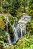 Ansicht des steinigen Wasserfalls und des kleinen Flusses Stockfotografie