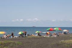 Ansicht des Strandes Touristen, sunbeds und Regenschirme am heißen Tag des Sommers Lizenzfreie Stockfotos