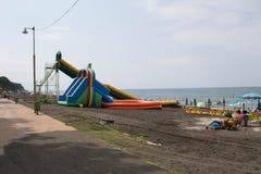 Ansicht des Strandes Touristen, sunbeds und Regenschirme am heißen Tag des Sommers Lizenzfreie Stockfotografie