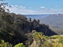 Ansicht des Tales und der Berge und drei Schwestern mit Eukalyptusbäumen an einem klaren Tag des blauen Himmels im Jamison Valley Lizenzfreies Stockfoto