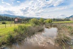 Ansicht des tiefen Nebenflusses, der Bauernhoffelder und der historischen Scheune an O-` Keefe Ranch lizenzfreies stockbild