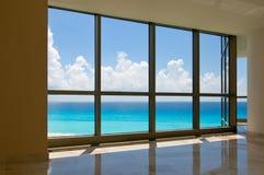 Ansicht des tropischen Strandes durch Hotelfenster Stockfotografie