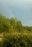 Ansicht des Waldes und des Regenbogens durch Fenster Lizenzfreie Stockfotografie