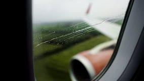 Ansicht durch das regnerische Fenster des Flugzeuges Rollbahn am Flughafen erfolgreich landend stockfoto
