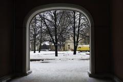 Ansicht durch den Bogen auf einer schneebedeckten Straße Stockfotografie