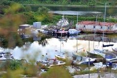 Ansicht durch die Büsche zum Pier mit Motorbooten und Booten entlang der Flussbank stockbild