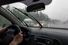 Ansicht durch die Regen-durchnäßte Windschutzscheibe unscharfe Schattenbilder Stockfotos