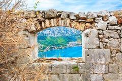 Ansicht durch ein Fenster in der alten Steinwand einer mittelalterlichen Festung zur Seelandschafts- und -küstenstadt lizenzfreies stockbild