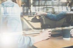 Ansicht durch ein Fenster, zwei junge Geschäftsfrauen, die bei Tisch sitzen und Gebrauchslaptop beim Trinken des Kaffees lizenzfreies stockfoto