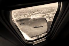 Ansicht durch einen Sepia mittlere Luft des Flugzeugfensters gefärbt Lizenzfreie Stockbilder