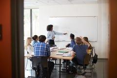 Ansicht durch Eingang der Highschool Tutor-At Whiteboard Teaching-Mathe-Klasse lizenzfreies stockbild