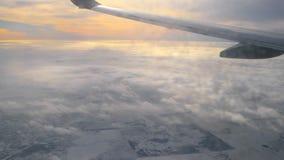 Ansicht durch schmutziges Fenster des Flugzeuges am Teil des Flügels und bewölkten des Himmels des Sonnenuntergangs stock video footage