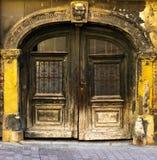 Ansicht einer alten enormen geschnitzten Holztür mit einem gestalteten Bogen und der gelben Fassade, Zagreb in Kroatien Lizenzfreies Stockbild