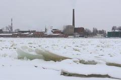 Ansicht einer alten Fabrik auf der Bank von einem gefrorenen Fluss Lizenzfreie Stockfotos
