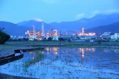 Ansicht einer Fabrik mitten in einem Ackerland mit den Kaminen, die am frühen Morgen Rauch ausstrahlen Stockfoto