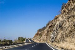 Ansicht einer Straße mit schwarzem Asphalt mit einem Steinberg dazu stockbilder