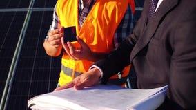 Ansicht eines Ingenieurs, der dem Kunden photo-voltaisches Detail an der Solarenergiestation zeigt stock footage