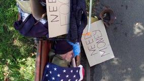 Ansicht eines obdachlosen Mannes, der auf Bank, sein Besitz nah an ihm schläft stock footage