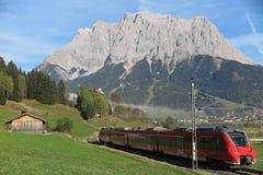 Ansicht eines Schnellzugs, der durch Grünfelder mit ausgezeichnetem Berg Zugspitze im Hintergrund reist Stockbild