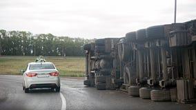 Ansicht eines umgeworfenen LKWs auf Landstraße im Unfall stockbilder