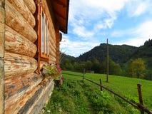 Ansicht entlang Wand des Holzhauses auf Berg und Wiese Stockbild