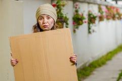 Ansicht im Freien der obdachlosen Frau leeres Pappzeichen halten Stockbild