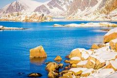 Ansicht im Freien des Schnees schmelzend über einem Felsen an der Küste am Freien im verschneiten Winter im nördlichen Polarkreis Lizenzfreies Stockfoto