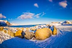 Ansicht im Freien des Schnees schmelzend über einem Felsen an der Küste am Freien im verschneiten Winter im nördlichen Polarkreis Stockfotografie