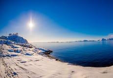 Ansicht im Freien des weißen Holzhauses am Ufer, alles Land, das mit Schnee bedeckt wird, Sonne shinny im Himmel mit blauem See h stockfoto