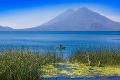 Ansicht im Freien von totora acuatic Anlagen in der Grenze des Sees, mit nicht identifiziertem Fischer in kleine Boote in Atitlan Stockbilder