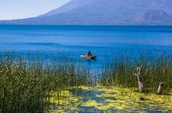 Ansicht im Freien von totora acuatic Anlagen in der Grenze des Sees, mit nicht identifiziertem Fischer in kleine Boote in Atitlan Lizenzfreie Stockbilder