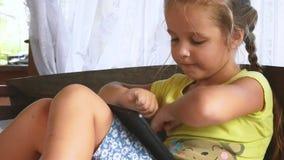 Ansicht-kaukasisches kleines Mädchen beim Bett-Lernen, spielend auf Tablet im Schlafzimmer stock video footage