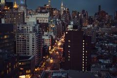 Ansicht New York City Manhattan zur beschäftigten Allee mit Autos im Verkehr nach Arbeitsstunde-Geschäftszeit Lizenzfreie Stockfotos