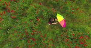 Ansicht oben von des netten jungen Mädchens, das bunten Regenschirm in einer Mohnblume spinnt Verbindung mit Natur Freizeit drau? stock video footage