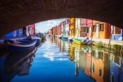 Ansicht unter Brücke von bunten venetianischen Häusern und von Booten in Inseln von Burano in Venedig, Italien lizenzfreie stockbilder