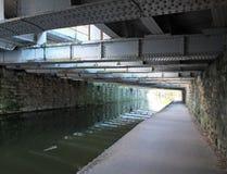 Ansicht unter eine alte niedrige Stahlbalkenbrücke, die das Leeds zu Liverpool-Kanal nahe armley mit Steinwand und einem schmalen stockbild