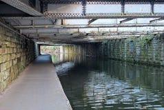 Ansicht unter eine alte niedrige Stahlbalkenbr?cke, die das Leeds zu Liverpool-Kanal nahe armley mit Steinwand und einem schmalen stockfoto